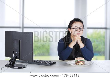 Image of obesity woman with computer and hesitate to eat cheeseburger at home