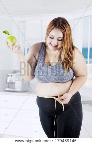 Portrait of an overweight woman measuring her belly with a measure tape while holding apple fruit and standing in the kitchen