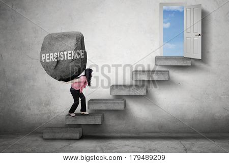 Picture of a strong female worker walking on the stairs while bringing a boulder toward a door