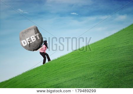 Female entrepreneur climbing a hill while carrying a big stone with text of Debt. Concept of big debt
