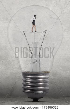 Businesswoman walking inside a big lamp while keeping her equilibrium shot with grey wall