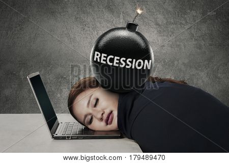 Female worker sleeping on her laptop with a text of recession on the bomb over her head