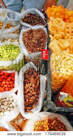 Mexican tradional snack sold by local stall in Mexico. There are fried grasshoppers(chapulines) with chili or garlic, peanut, pistachio nuts, fried peas and cookies.