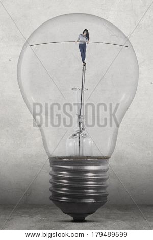 Picture of a young businesswoman walking inside a big lamp while holding a stick to keep her balance