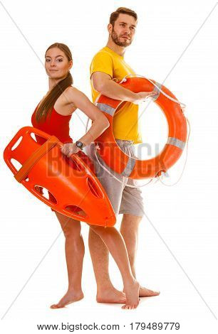 Lifeguards with rescue tube and ring buoy lifebuoy. Man and woman supervising swimming pool. Accident prevention.