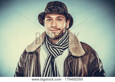 Portrait of happy man with half shaved face beard hair in hat scarf and jacket. Smiling handsome guy on blue. Skin care hygiene and fashion. Instagram cross filter.