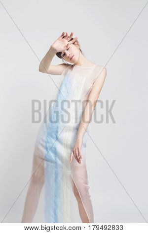 Fashion model with dark hair in a white and blue dress on a light background. Creative fashion photo. Geometric poses. Creative makeup. A model with a bang.