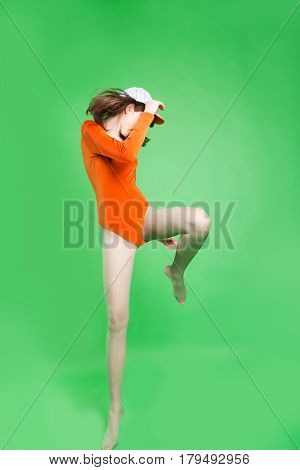 Fashion model with dark hair in an orange body and cap on a green background background. Creative fashion photo. Geometric poses. Creative makeup. Model with a bang and big ears. Makeup with blue and white eye shadow and smeared lipstick. Woman jumping