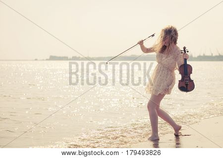 Music love hobby and everyday passion concept. Woman on beach near sea holding violin playing in water