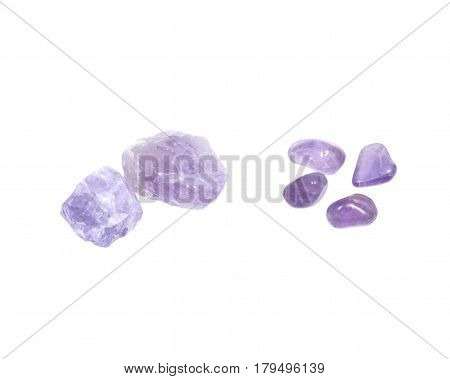 Amethyst: natural chunks from Madagascar and tumbled stones from Brazil isolated on white background
