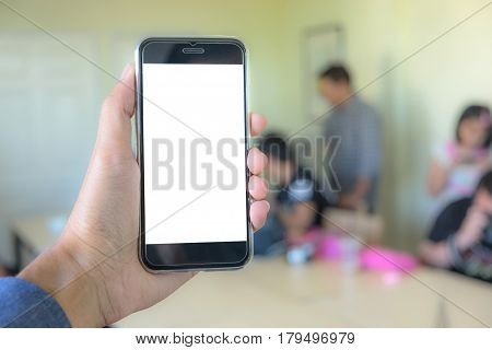 Man using smartphone in cafe. hand holding smart phone white screen. black color smart phone vintage tone. hand holding using mobile phone.