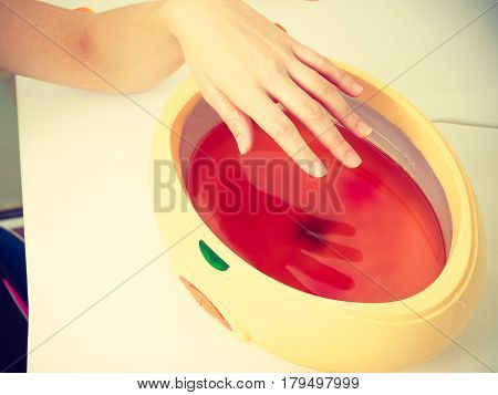 Woman Getting Paraffin Hand Treatment At Beautician