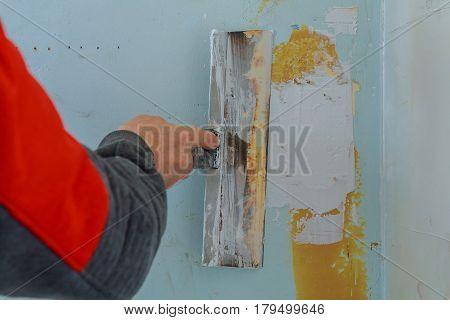 Male builder makes repairs in the apartment plaster trowel tools