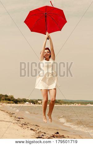 Redhead Woman Walking On Beach Jumping With Umbrella