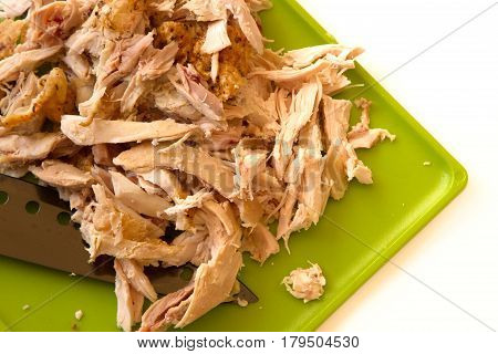 Shredded Rotisserie Chicken On A Green Cutting Board And Carving Knife Isolated On A White Backgroun
