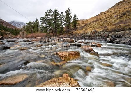 Cache Le Poudre River flows through the Poudre canyon west of Fort Collins Colorado on a gloomy day