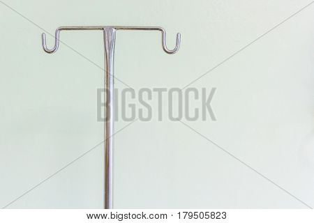 Empty intravenous pole hanger for serum blood and pharmaceutical bags in brightly lit hospital room at treatment end.