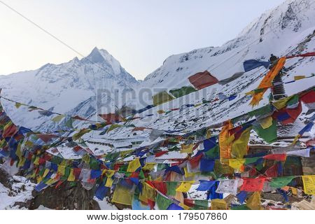 ANNAPURNA, NEPAL -  APRIL 14, 2016 : Prayer flags and snow mountain of Himalaya Annapurna base camp with Machapuchare peak in background Nepal