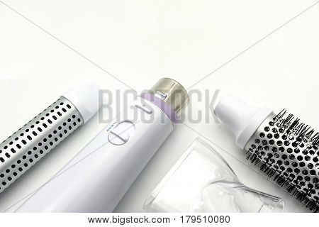 Collection electric hair dryer and hair curler in beauty salon isolate on white background Top view with copy space and text.