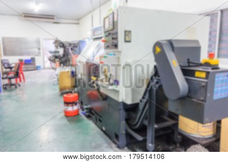 CNC machine with lathes at factory metal machining shop. blurred photo background