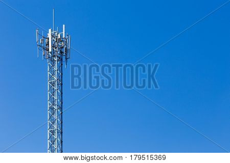 telecommunication cellular tower against cloudy blue sky with room for copy space