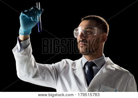 science, medicine, chemistry, research and people concept - young scientist in safety glasses with test tube