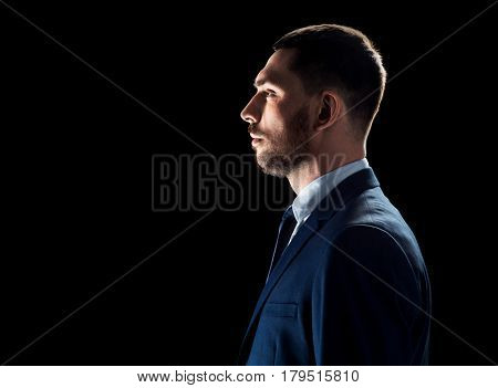 business, people and office concept - buisnessman in suit over black background