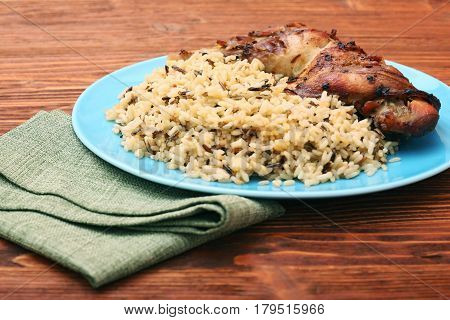 Roasted turkey leg with wild rice on wooden background