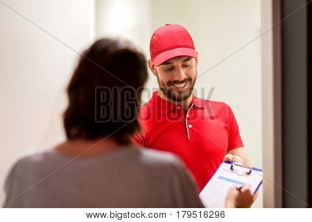 delivery, mail, people and shipping concept - happy man with clipboard and customer signing form at home