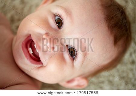 childhood, babyhood, emotions and people concept - close up of happy little baby boy or girl face