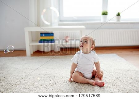 childhood, babyhood and people concept - happy little baby boy or girl sitting on floor with soap bubbles around at home