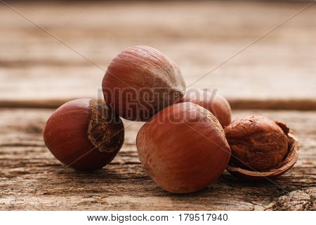 Filbert nuts on wood close-up. Several hazelnuts with one peeled. Brown autumn background. Harvest, fall, food ingredient concept
