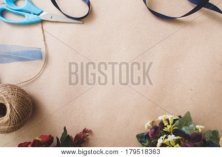Handmade art background, flat lay. Creative handiwork, making decorations from artificial colorful flowers. Ribbons, rope and scissors frame on beige background with copy space for text.