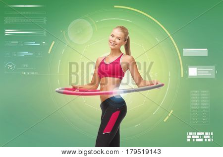 fitness, sport, power, technology and people concept - young sporty woman with hula hoop over green background