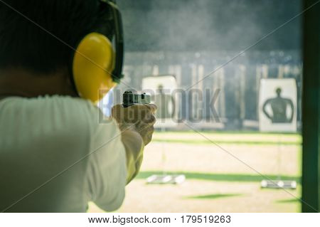 law enforcement aimimg and shooting gun in academy shooting range surround with smoke and copy space