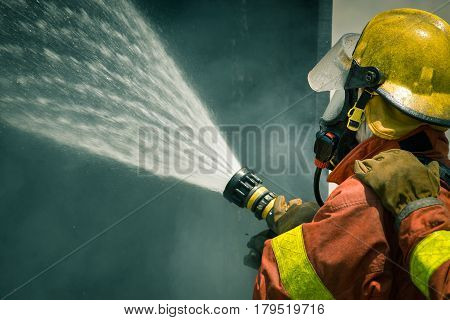 firefighter water spray by high pressure fire hose with copy space in cinematic tone