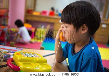 4 years old Asian boy playing pick up toy phone in toy room