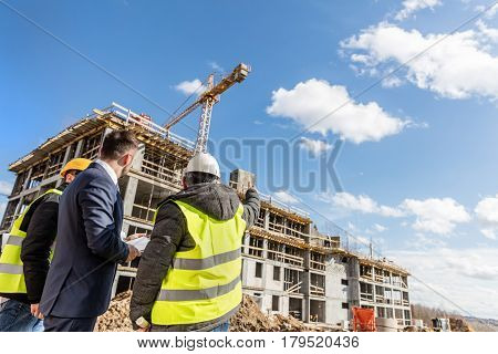 Engineers and investor meeting at the construction site. Engineer showing the progress in work. Real estate market.