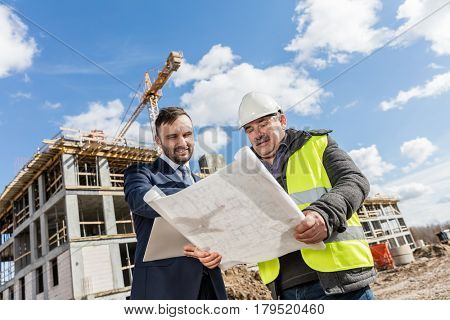 Engineer and investor meeting at the construction site. Discussing the building plans. Real estate market.