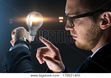 business, people and modern technology concept - close up of businessman with smart watch and lightbulb projection over black background