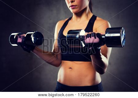 sport, fitness, bodybuilding, weightlifting and people concept - close up of woman flexing arms with dumbbell in gym