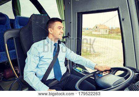 transport, tourism, road trip and people concept - happy driver talking to microphone and driving bus