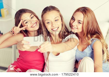 friendship, people, pajama party and technology concept - happy friends or teenage girls with smartphone taking selfie at home poster