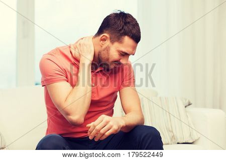 people, healthcare and problem concept - unhappy man suffering from neck pain at home