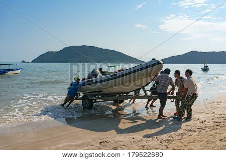 People Pulling Boat On Shore