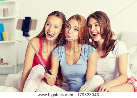 friendship, people, pajama party and technology concept - happy friends or teenage girls with smartphone and monopod taking selfie at home