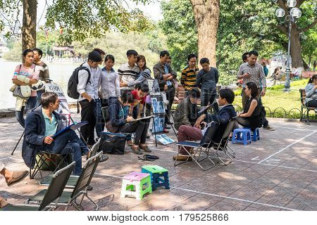 Hanoi Vietnam - February 17 2016: Asian portrait painter drawing sketch of customer by pencil on the sidewalk of Hoan Kiem lake in Hanoi Vietnam