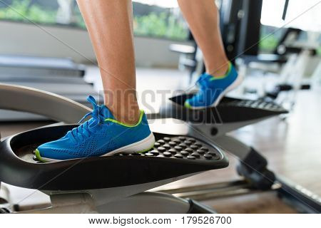 Woman doing exercise on elliptical trainer in gym