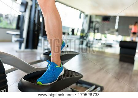 Sport woman working out on elliptical trainer in gym