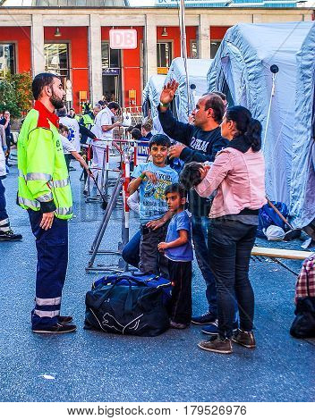 Munich,Germany-September 12,2015:A paramedic talks to a newly arrived migrant family at Munich Central Station